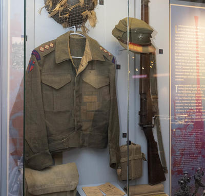 Elements of the uniform of a second world war Canadian soldiers are displayed in a case on a wall.