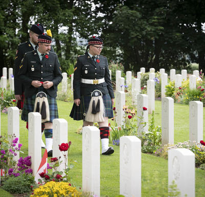 Three men in uniforms are walking in between two rows of tombstones in Bény-sur-Mer Canadian War Cemetery.