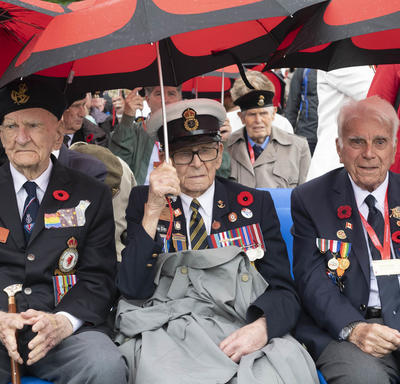 Three war veterans are seated in a front row of an audience with red and black umbrellas.