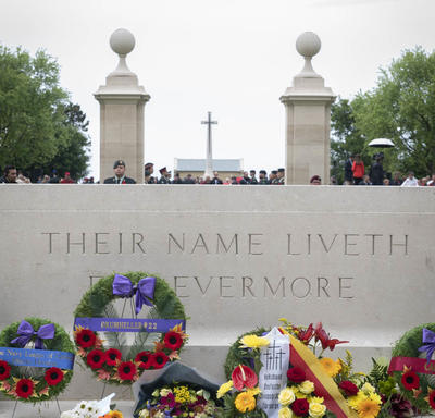 Flowers are laid in front of a monument at the Bény-sur-Mer Canadian War Cemetery.