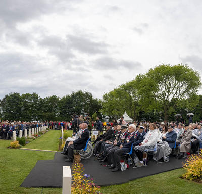 A crowd is seated during a ceremony at he Bény-sur-Mer Canadian War Cemetery.