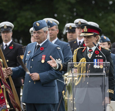 Governor General Julie Payette, wearing the Canadian Air Force uniform, is delivering remarks at a podium. she is surrounded by military members.