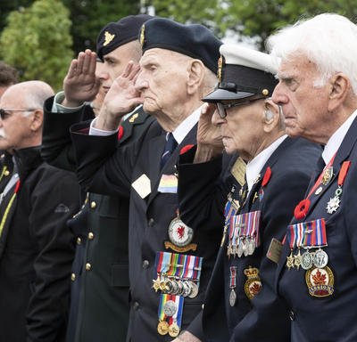 Elderly men, including veterans, are standing in a row. Veterans are saluting.