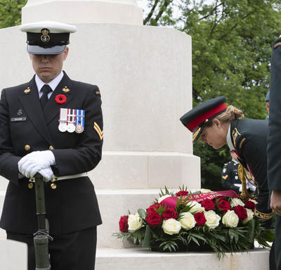 Governor General Julie Payette is laying a wreath at the foot of a white monument.