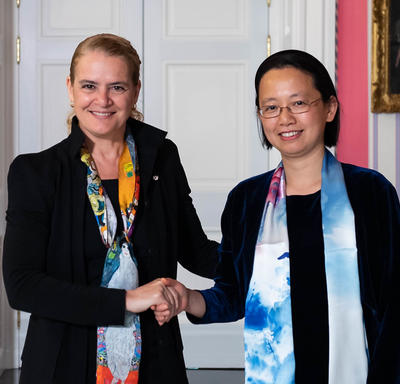 Lin Cai is shaking hands with the Governor General.