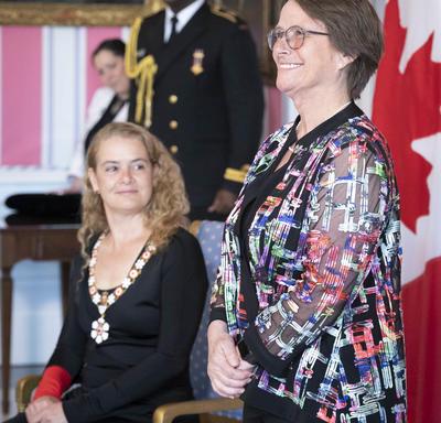 Claudine Roy se tient à l'avant de la salle avec la gouverneure générale.