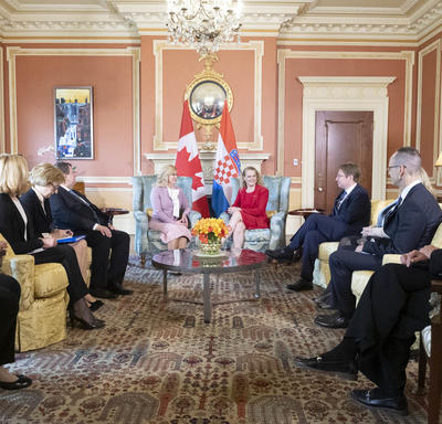 The President of the Republic of Croatia and the Governor General are sitting in chairs speaking to each other.