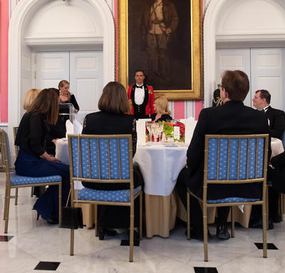 Photo of the head table and the Governor General delivering remarks from a podium at the State dinner.