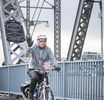 A cyclist on Alexandria Bridge waves