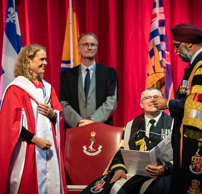 The Governor General stands to receive a Doctor of Laws honoris causa. The Honourable Harjit S. Sajjan, Minister of National Defence stands beside her.