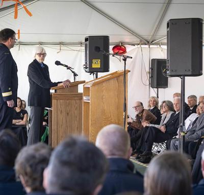 Mme Martha Miller, 92 ans, s'adresse à un auditoire assis, sous une tente blanche, à un podium.