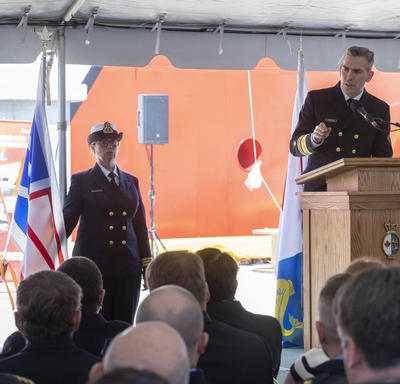 Jeffery Hutchinson, Commissioner if the Canadian Coast Guard, is speaking at a podium in front of a seated audience, under a white tent. A women wearing the Canadian Coast Guard Uniform is standing behind him, to his left, next to the Coast Guard flag.