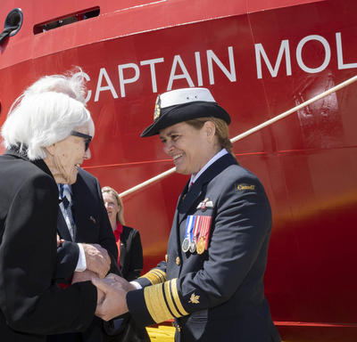 Ms. Martha Miller, 92 years old, is shaking hands with Governor General Julie Payette, in front of the Captain Molly Kool ship.