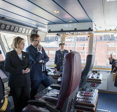 A group of 4 people including Governor General Julie Payette is listening to a Canadian Coast Guard official, inside the cockpit of the ship Captain Molly Kool.