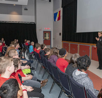 A group of students of grades 1 to 6 are seated in chairs in front of Governor General Julie Payette, during a Power Point presentation.