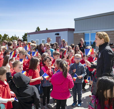Governor General Julie Payette is outside, on a sunny day, meeting with a large group of elementary school students.