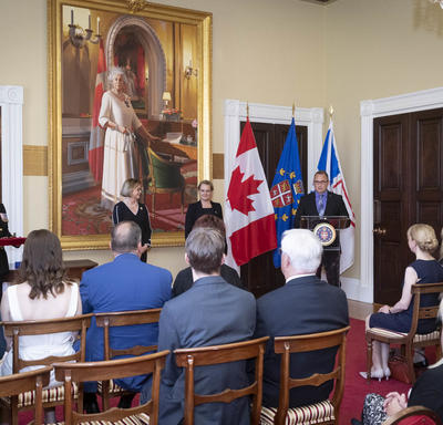 Governor General of Canada Julie Payette is standing in front of a small seated audience, while a gentleman is speaking at a podium  on her left. A large painting of Her Majesty Queen Elizabeth II is hanging behind her.