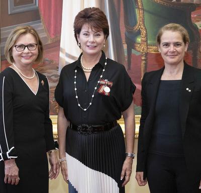 Une grande rousse se tient entre Judy May Foote, lieutenante-gouverneure de Terre-Neuve-et-Labrador, et la gouverneure générale Julie Payette.