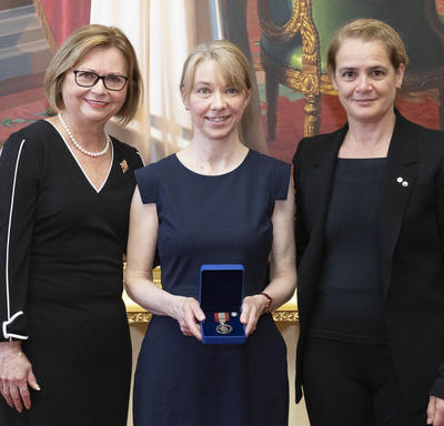 Une femme blonde tient une médaille dans une boîte de velours bleu entre Judy May Foote, lieutenante-gouverneure de Terre-Neuve-et-Labrador et Julie Payette, gouverneure générale.