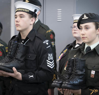 Cadets are holding boots in their hands.