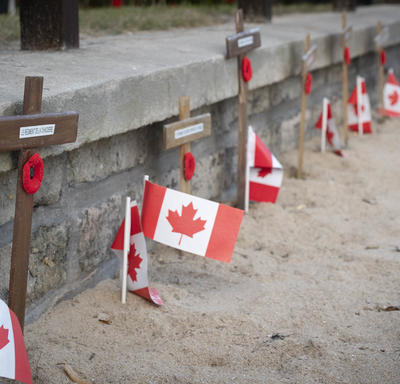 Crosses and Canadian flags in a row.