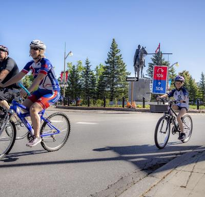 A family cycles by the Queen Elizabeth II statue on Sussex Drive