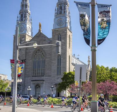Participants cycle past the Notre-Dame Cathedral Basilica on Sussex Drive