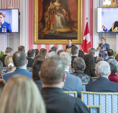 A photo of the room during the ceremony, with the Governor General speaking at the podium, displayed on two screens.