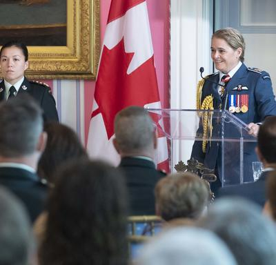 The Governor General delivers remarks at a podium, an aide-de-camp stands nearby.