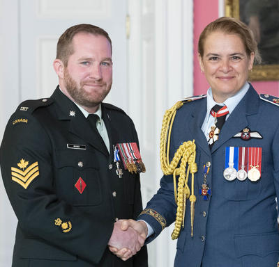 Master Corporal Archer shakes hands with the Governor General after receiving his medal.