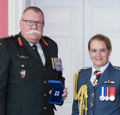 Brigadier-General Anderson accepts his medal from the Governor General and poses for a photo.