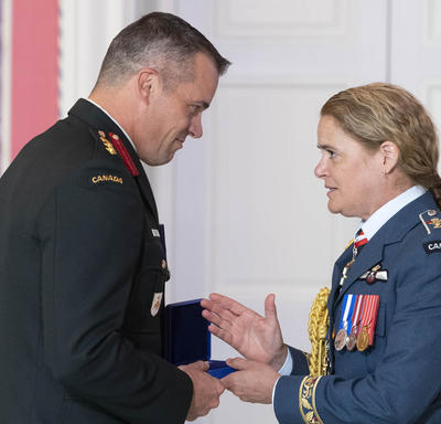 Colonel Huet accepts his medal and shakes hands with the Governor General.
