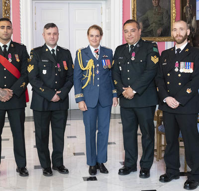 Petty Officer 1st Class Charles Bressette, Sergeant Andrea Karistinos and master corporals Kashif Dar and Jesus Castillo take a photo with the Governor General.