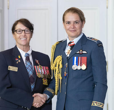 Debra Reid accepts her medal and poses for a photo with the Governor General.
