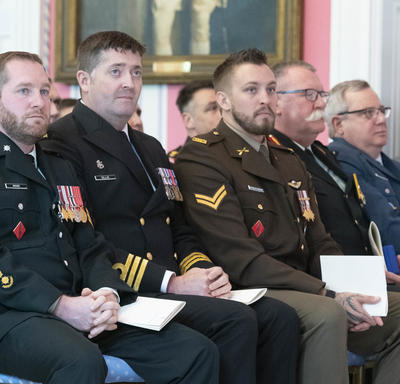 Recipients of the military-themed ceremony sit in the front row and look on as other recipients are awarded.