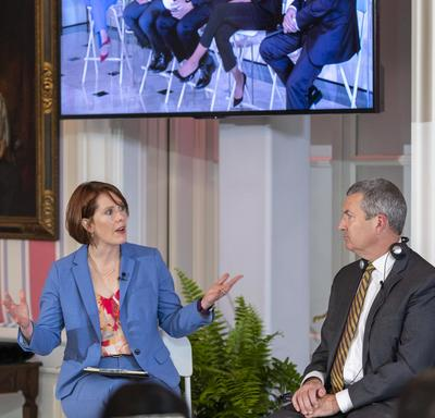 Alison Crawford, wearing a blue pant suit, is siting on a white tall stool, talking to David Aiken, wearing a grey suit and seated at a tall white stool. A large tv screen above them shows a panel of 5 people.