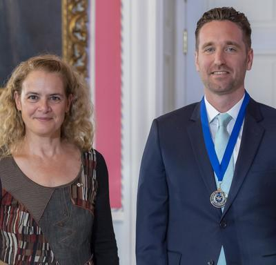 Governor General of Canada Julie Payette and reporter Corbett Hancey, wearing a medal with a blue ribbon, are standing looking directly at the camera.