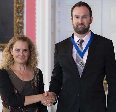 Governor General of Canada Julie Payette and reporter Greg Mercer, wearing a medal with a blue ribbon, are standing looking directly at the camera.