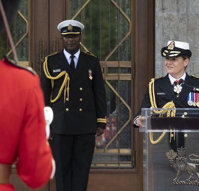 The Governor General delivers a speech at a podium with her aide-de-camp by her side.