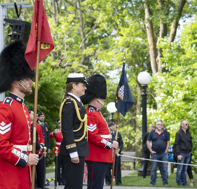 The Governor General stands between two guards as they watch the Ceremonial Guard in silent admiration.
