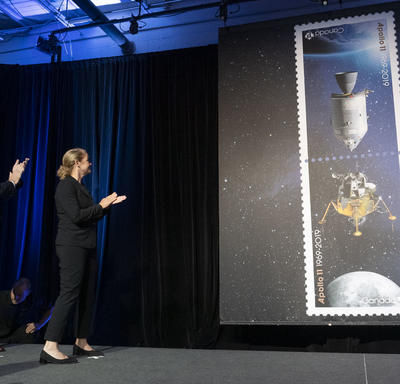 The Governor General claps on stage as the Apollo 11 stamps are unveiled.