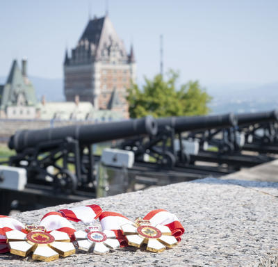 A picture of the Order of Canada Medals, laid out on a stone wall, with cannons and the Chateau Frontenac in the background.