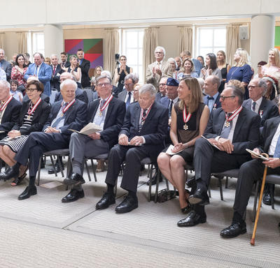Guests in attendance cheer and congratulate the newly invested members of the Order of Canada.