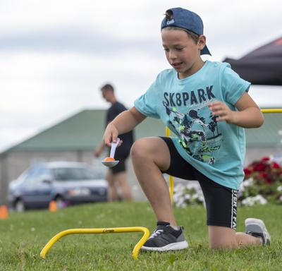 A young boy is doing an obstacle course.