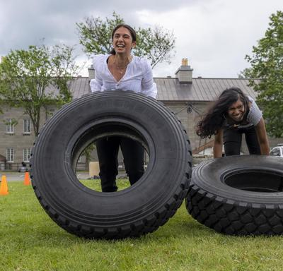 Two women are flipping tires as part of an obstacle course.