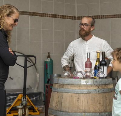 The Governor General speaks with a young girl and Laurence-Olivier Brassard inside the winery, where bottles of wine are displayed on a barrel.