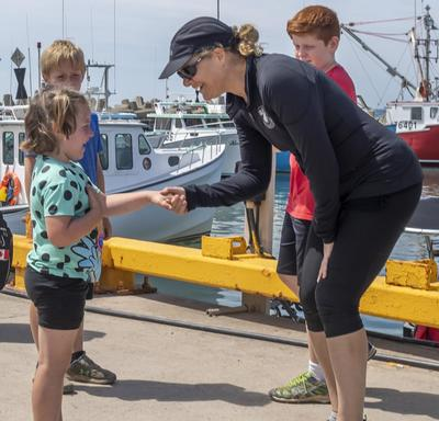 The Governor General meets and shakes hands with a young girl in the port of Île d'Entrée.