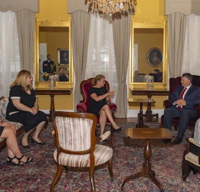 The Governor General, Her Honour the Honourable Antoinette Perry, Lieutenant Governor of Prince Edward Island, and the Honourable Dennis King, Premier of Prince Edward Island, sit and discuss with other delegates in a room inside Government House.