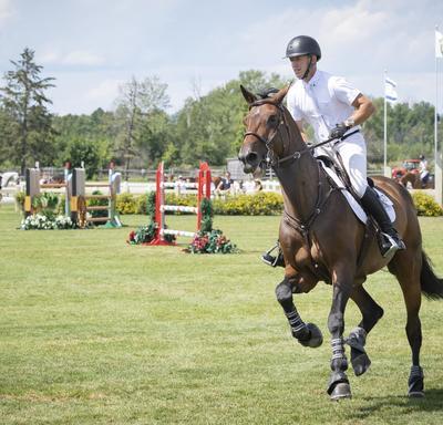 Vue de face d'un cavalier et sa monture  qui tournent vers la droite dans un parcours extérieur lors d'une compétition.