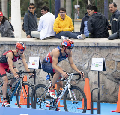 Men's triathletes entered the transition section on their bikes.